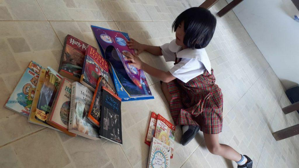 Una delle bambine di Isla Ng Bata mentre legge un libro di Book-Cycle nelle Filippine.